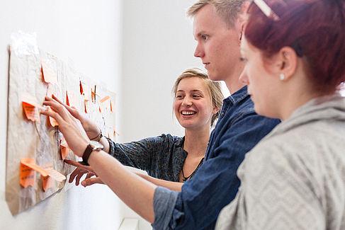 Drei Studierende an einer Pinnwand